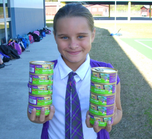 student holding cat food cans